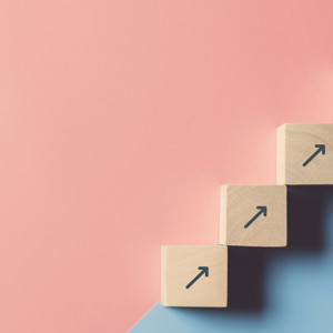 Business concept growth success process, Close up man hand arranging wood block stacking as step stair on paper blue and pink background, copy space.