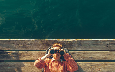 Young Girl In Orange Jacket Lies On A Pier Near The Sea And Looks Through Binoculars. Travel Search Journey Concept