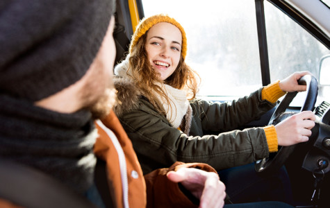 Beautiful young couple on a trip in winter, close up of girl driving.