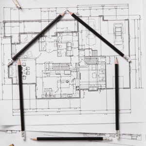 Top view of architectural blueprints, rolls and drawing instruments on the worktable. Shape of house with black pencils on a project house. Architectural drawings with house keys on wooden table, new home concept.