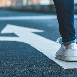 Female shoes walking on arrow on street