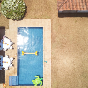 house backyard with swimming pool above drone view on sunny day